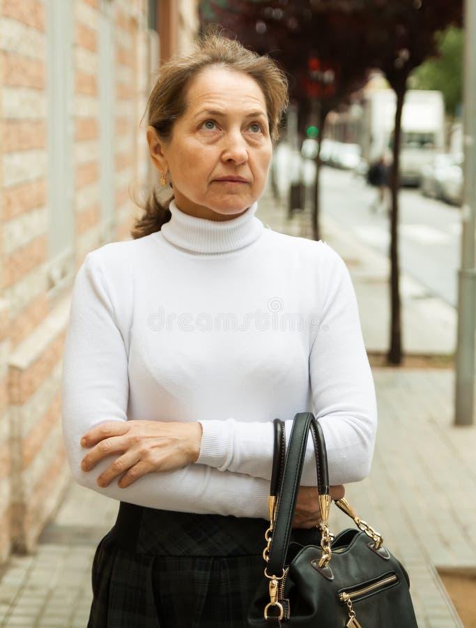 Ώριμη γυναίκα στο πεζοδρόμιο στοκ φωτογραφία με δικαίωμα ελεύθερης χρήσης