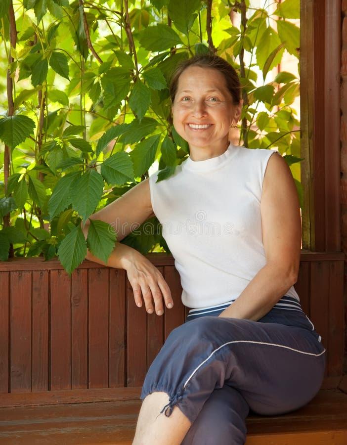 Ώριμη γυναίκα στο summerhouse στοκ φωτογραφία
