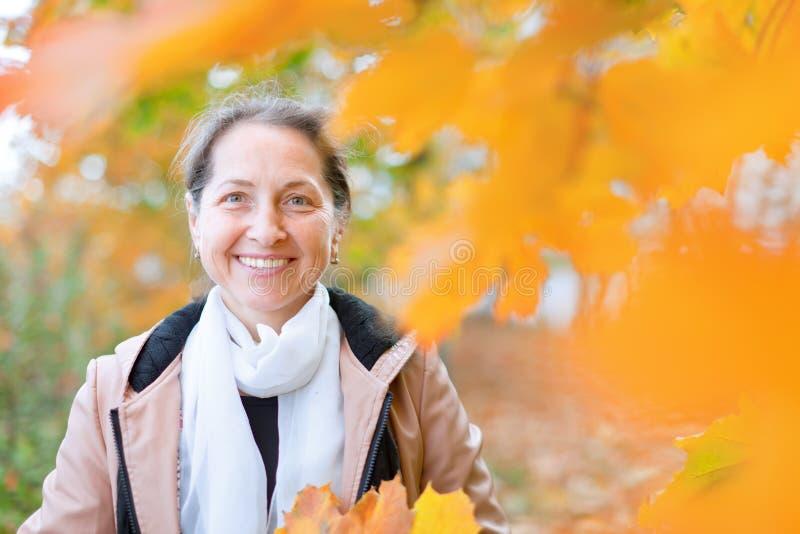 Ώριμη γυναίκα το φθινόπωρο στοκ φωτογραφία