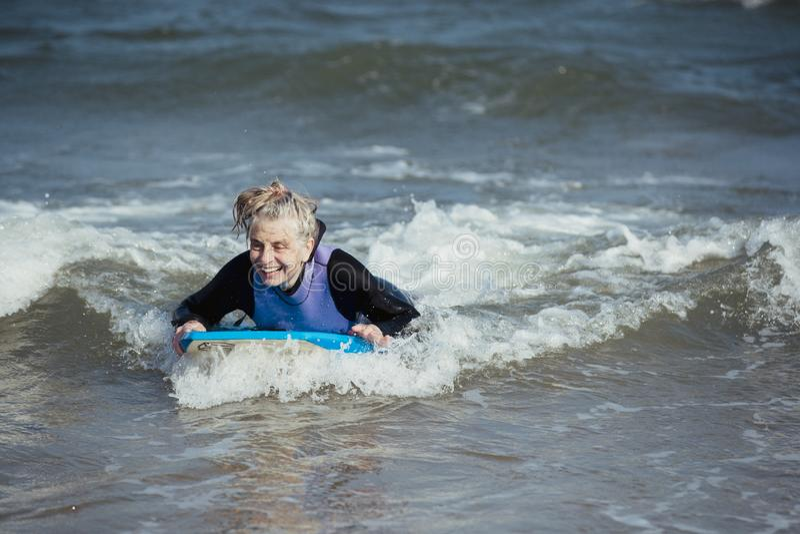 Ώριμη γυναίκα Bodyboarding στη θάλασσα στοκ εικόνες