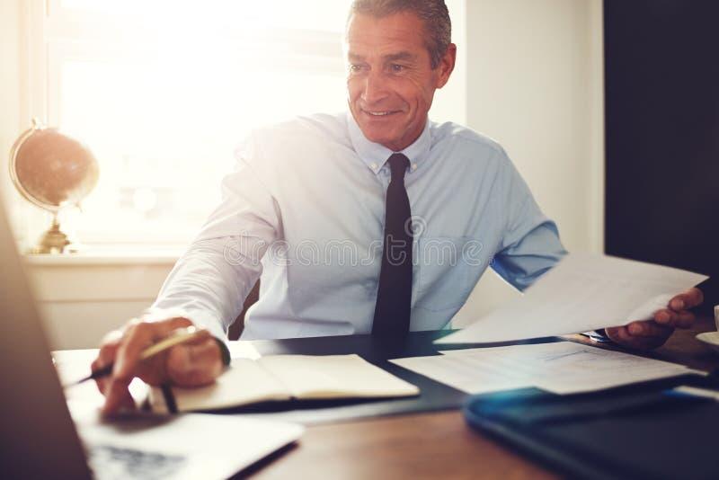 Ώριμη εκτελεστική εργασία χαμόγελου στο γραφείο του σε ένα γραφείο στοκ εικόνα με δικαίωμα ελεύθερης χρήσης
