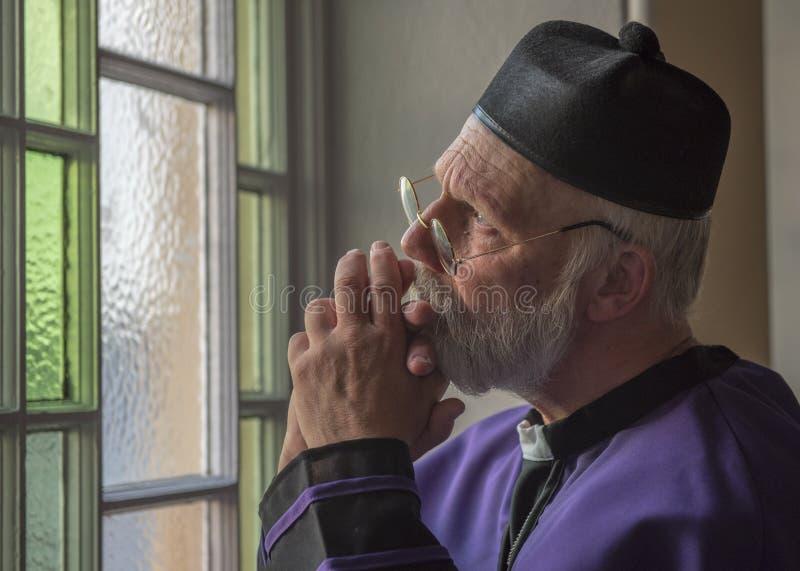 Ώριμη επίκληση ιερέων, που κοιτάζει έξω μέσω ενός παραθύρου στοκ εικόνες