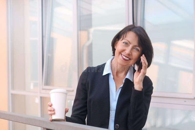 Ώριμη επιχειρηματίας που έχει ένα κενό μπροστά από ένα κτίριο γραφείων, που μιλά στο τηλέφωνο και τον καφέ κατανάλωσης στοκ εικόνες