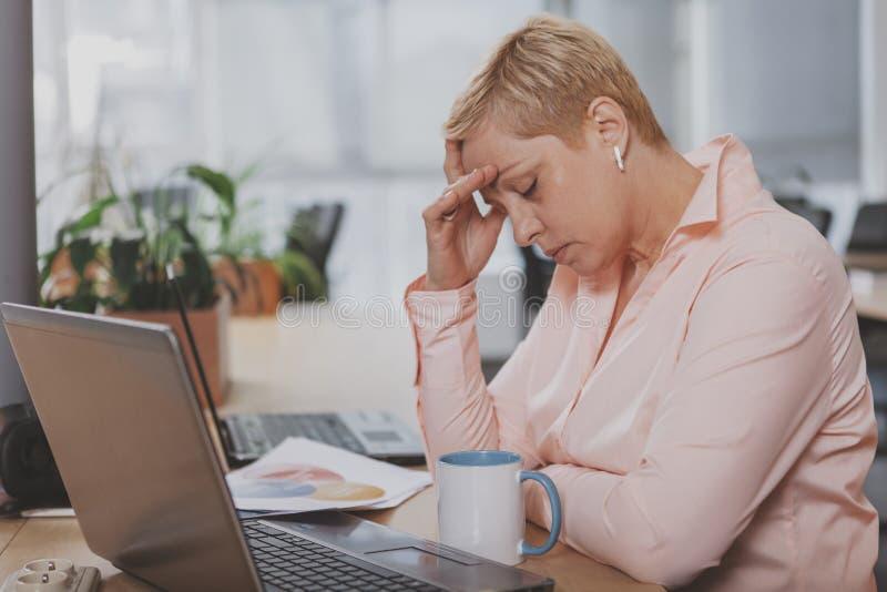 Ώριμη επιχειρηματίας που εργάζεται στο γραφείο στοκ εικόνα