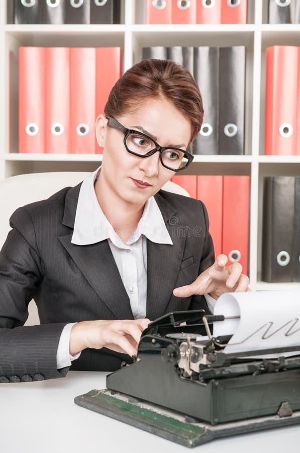 Ώριμη επιχειρησιακή γυναίκα που εργάζεται με τη γραφομηχανή στοκ εικόνες