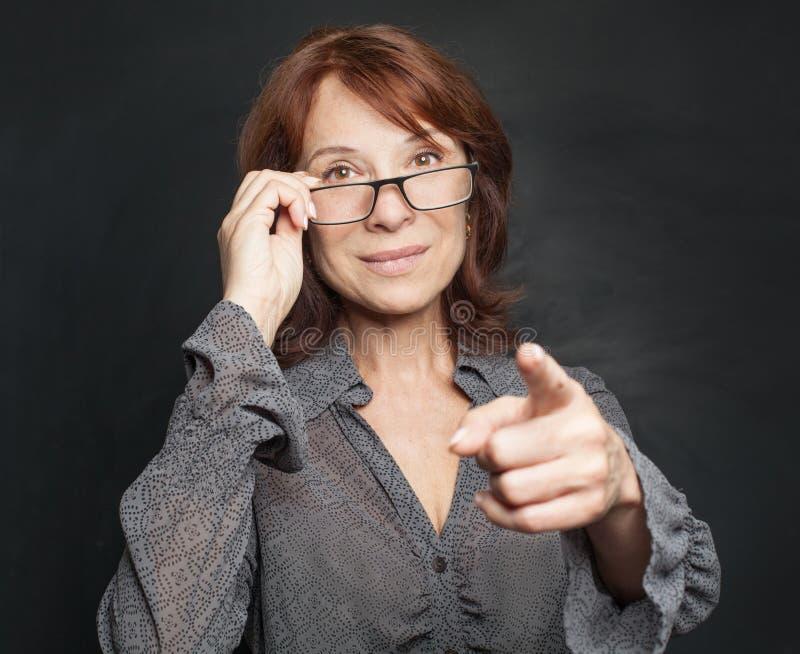 Ώριμη επιχειρησιακή γυναίκα στην υπόδειξη γυαλιών στοκ φωτογραφία με δικαίωμα ελεύθερης χρήσης