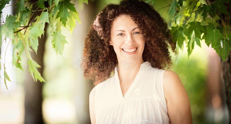 Ώριμη Ισπανίδα Που Χαμογελά Στην Κάμερα Είναι έξω στο πάρκο Τόσο χαρούμενη στοκ εικόνες