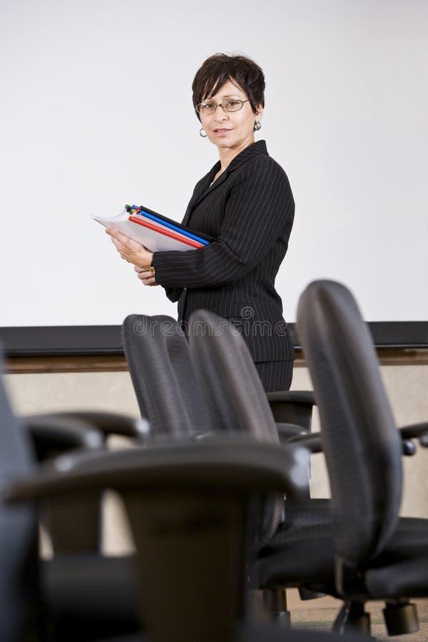 Ώριμη ισπανική επιχειρησιακή γυναίκα που υπερασπίζεται τις έδρες στοκ φωτογραφίες
