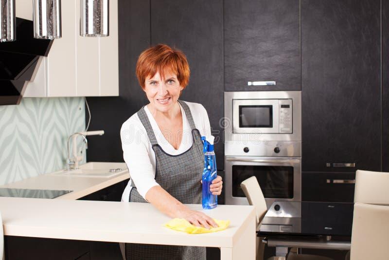 Ώριμη καθαρίζοντας κουζίνα γυναικών στοκ εικόνα