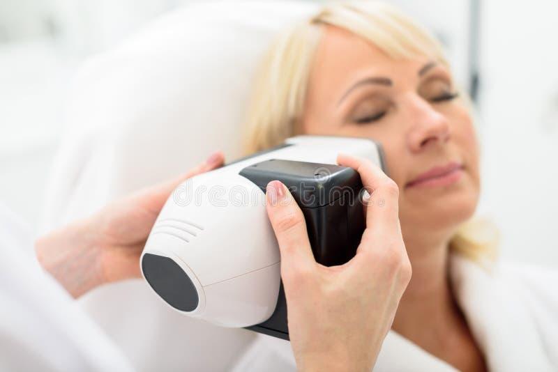 Ώριμη κυρία που απολαμβάνεται την αναζωογόνηση δερμάτων από το massager στοκ φωτογραφίες