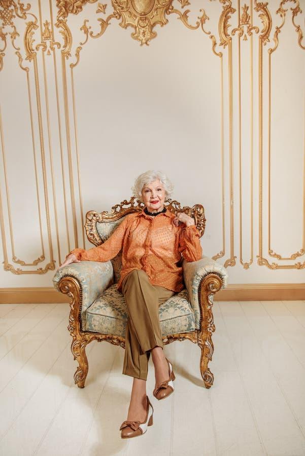 Ώριμη κυρία που στηρίζεται στην πανέμορφη καρέκλα στοκ φωτογραφίες