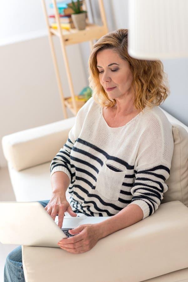 Ώριμη κυρία που χρησιμοποιεί τον υπολογιστή στο σπίτι στοκ εικόνα με δικαίωμα ελεύθερης χρήσης
