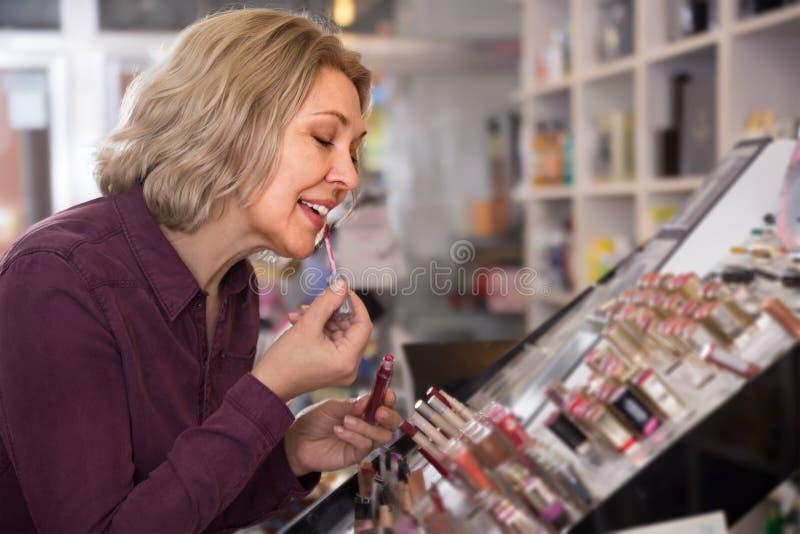 Ώριμη ξανθή γυναίκα που επιλέγει το χείλι πιό παχουλό στην επίδειξη στοκ φωτογραφίες