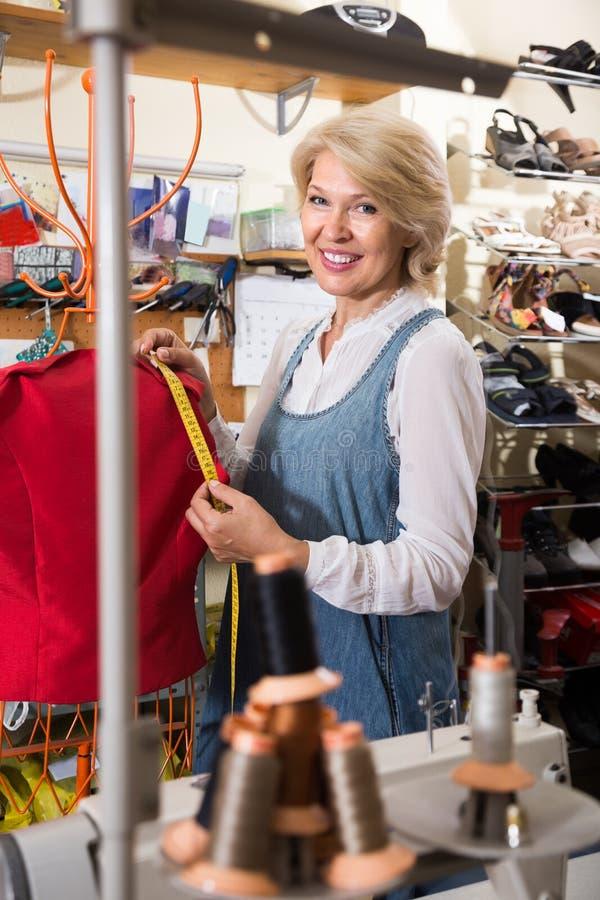 Ώριμη ράβοντας εσθήτα γυναικών στο κατάστημα ιματισμού στοκ φωτογραφία με δικαίωμα ελεύθερης χρήσης