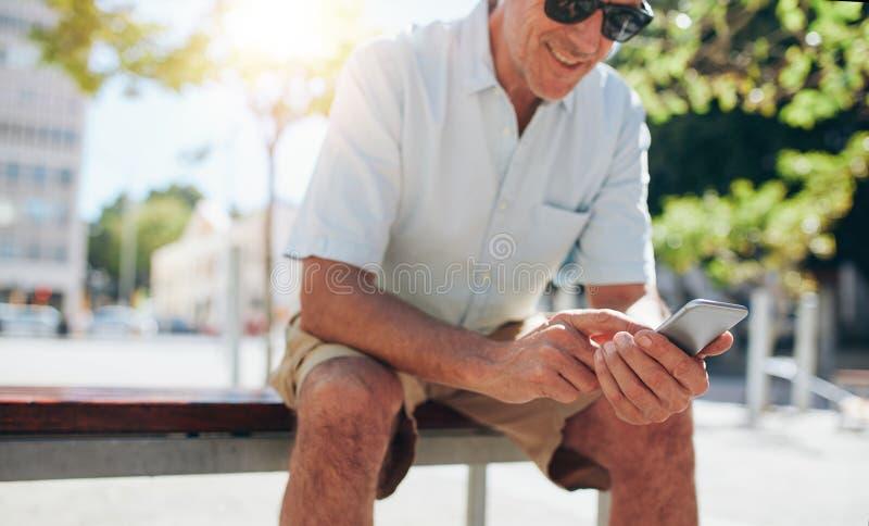 Ώριμη συνεδρίαση ατόμων που χρησιμοποιεί υπαίθρια το κινητό τηλέφωνο στοκ εικόνα
