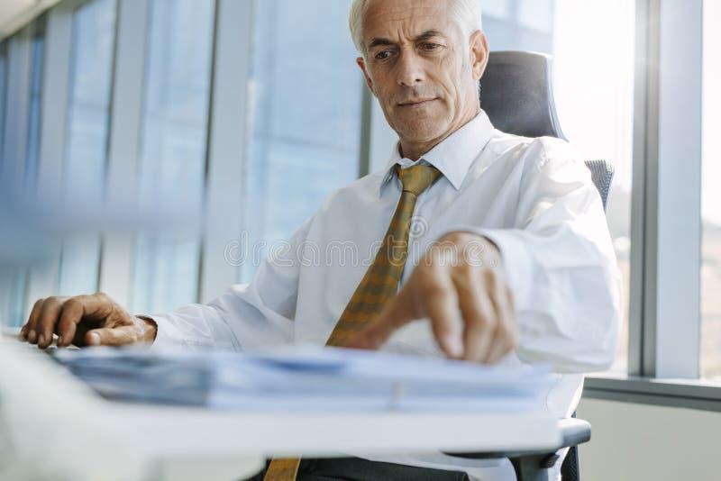 Ώριμη συνεδρίαση επιχειρηματιών στο γραφείο του και εργασία στοκ εικόνα