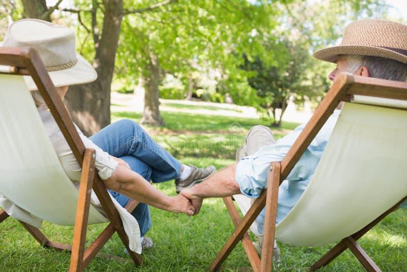 Ώριμη συνεδρίαση ζευγών στις καρέκλες γεφυρών στο πάρκο στοκ φωτογραφία με δικαίωμα ελεύθερης χρήσης