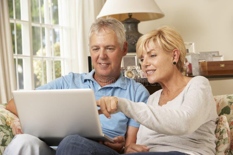 Ώριμη συνεδρίαση ζεύγους στον καναπέ που χρησιμοποιεί στο σπίτι το lap-top στοκ φωτογραφία
