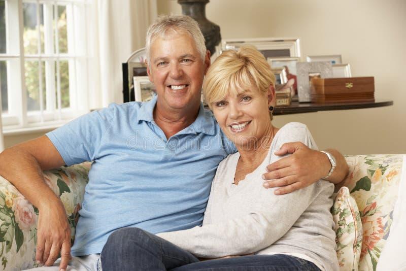 Ώριμη συνεδρίαση ζεύγους στον καναπέ στο σπίτι από κοινού στοκ φωτογραφίες