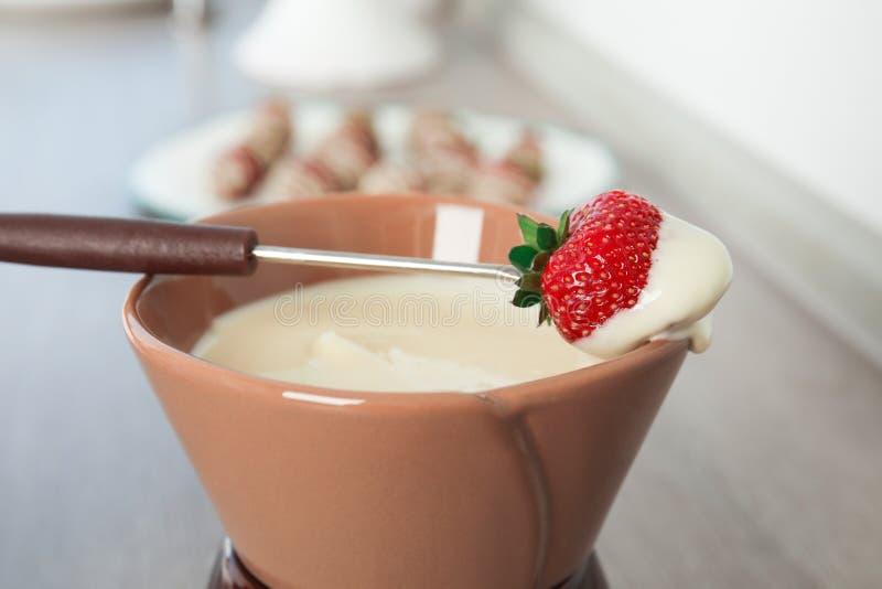 Ώριμη φράουλα που βυθίζεται στο άσπρο fondu σοκολάτας στοκ εικόνα