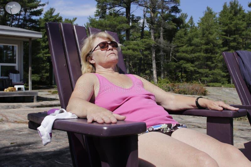 Ώριμη χαλάρωση γυναικών σε μια καρέκλα παραλιών στο εξοχικό σπίτι ηλικίας 60 έως 70 στοκ εικόνα με δικαίωμα ελεύθερης χρήσης
