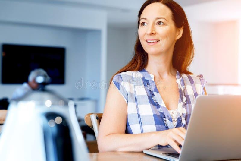 Ώριμη όμορφη γυναίκα που εργάζεται στο lap-top της στοκ εικόνα