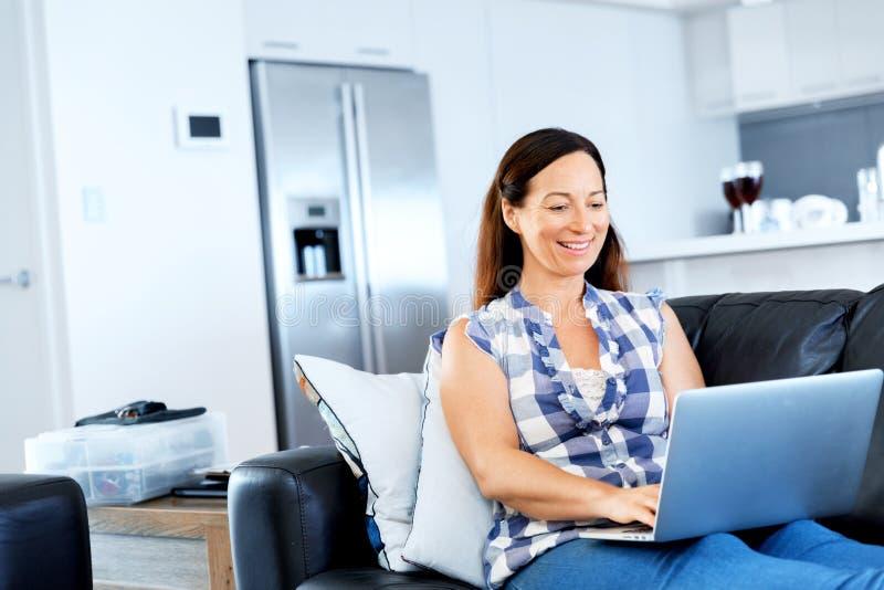 Ώριμη όμορφη γυναίκα που εργάζεται στο lap-top της στοκ εικόνα με δικαίωμα ελεύθερης χρήσης