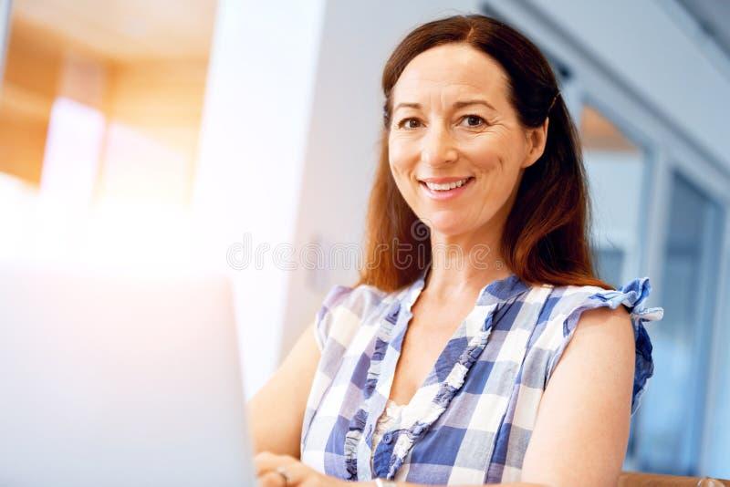 Ώριμη όμορφη γυναίκα που εργάζεται στο lap-top της στοκ φωτογραφίες