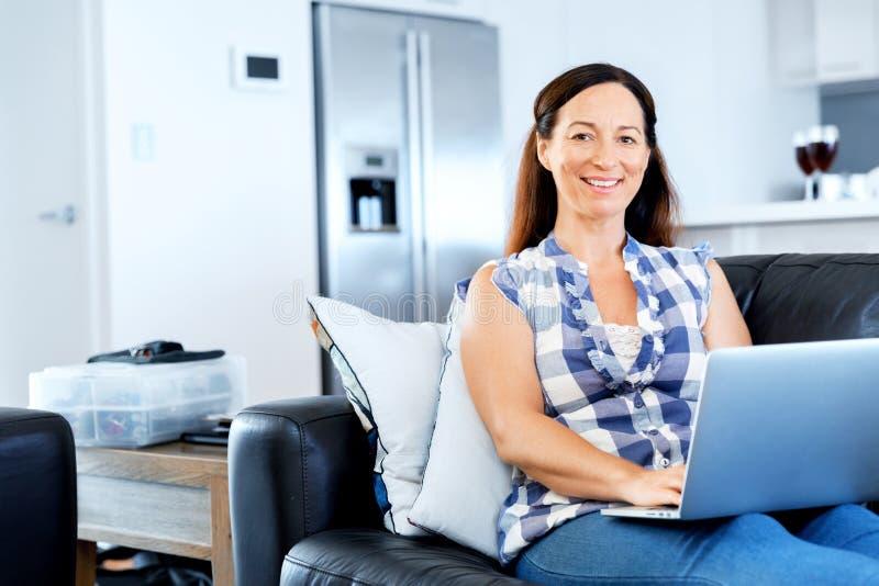 Ώριμη όμορφη γυναίκα που εργάζεται στο lap-top της στοκ φωτογραφία με δικαίωμα ελεύθερης χρήσης