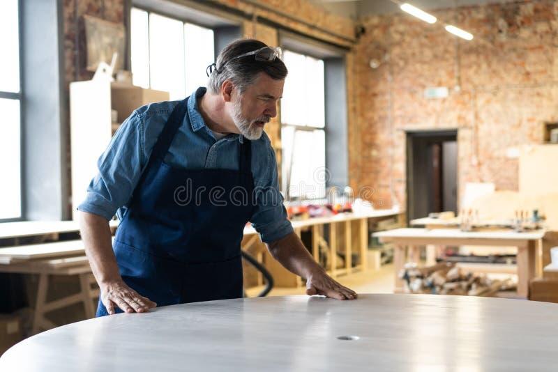 Ώριμη όμορφη εργασία ξυλουργών στην ξυλουργική Είναι επιτυχής επιχειρηματίας στον εργασιακό χώρο του στοκ εικόνα με δικαίωμα ελεύθερης χρήσης