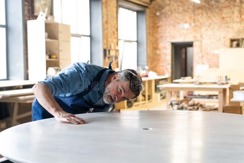 Ώριμη όμορφη εργασία ξυλουργών στην ξυλουργική Είναι επιτυχής επιχειρηματίας στον εργασιακό χώρο του στοκ φωτογραφία