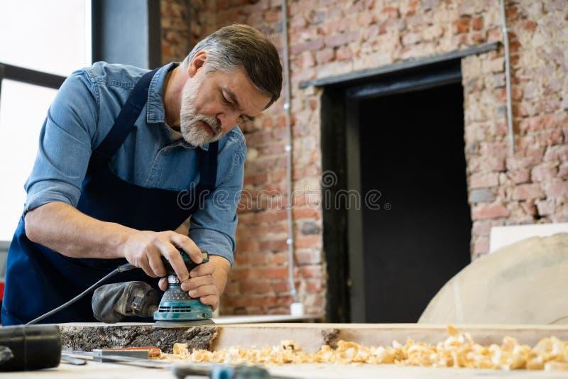 Ώριμη όμορφη εργασία ξυλουργών στην ξυλουργική Είναι επιτυχής επιχειρηματίας στον εργασιακό χώρο του στοκ φωτογραφία με δικαίωμα ελεύθερης χρήσης