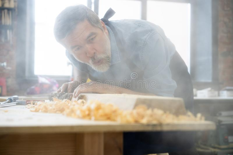 Ώριμη όμορφη εργασία ξυλουργών στην ξυλουργική Είναι επιτυχής επιχειρηματίας στον εργασιακό χώρο του στοκ εικόνες