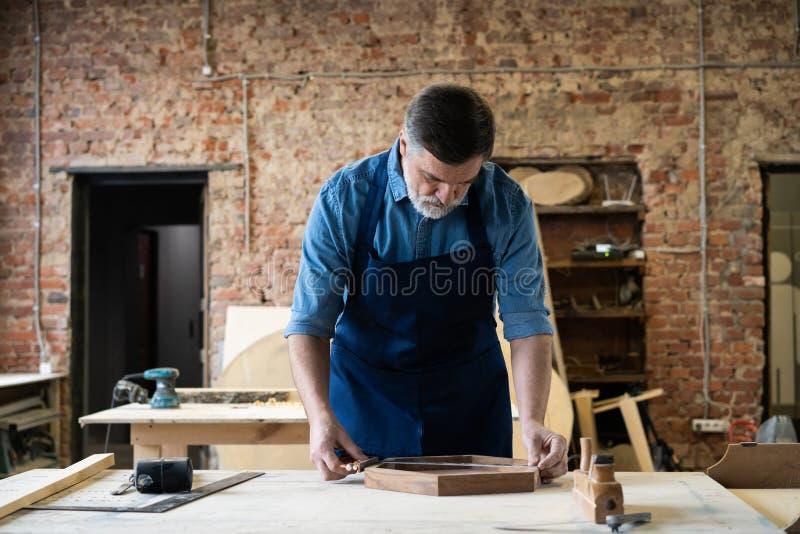 Ώριμη όμορφη εργασία ξυλουργών στην ξυλουργική Είναι επιτυχής επιχειρηματίας στον εργασιακό χώρο του στοκ φωτογραφίες με δικαίωμα ελεύθερης χρήσης