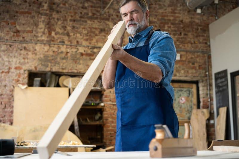 Ώριμη όμορφη εργασία ξυλουργών στην ξυλουργική Είναι επιτυχής επιχειρηματίας στον εργασιακό χώρο του στοκ εικόνα