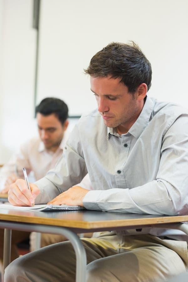 Ώριμοι σπουδαστές που παίρνουν τις σημειώσεις στην τάξη στοκ εικόνες