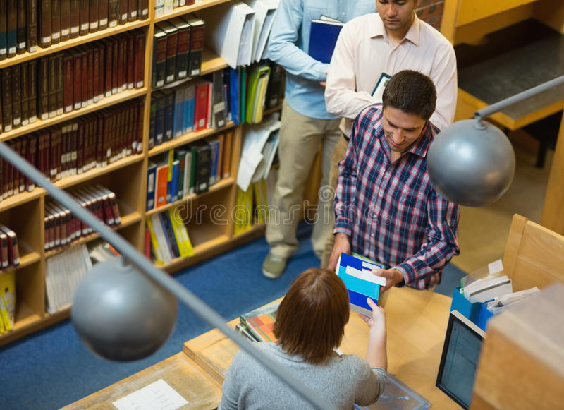 Ώριμοι σπουδαστές στο μετρητή στη βιβλιοθήκη κολλεγίων στοκ εικόνα με δικαίωμα ελεύθερης χρήσης