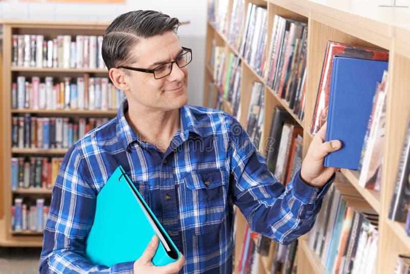 Ώριμος άνδρας σπουδαστής που παίρνει το βιβλίο από το ράφι στη βιβλιοθήκη στοκ εικόνες