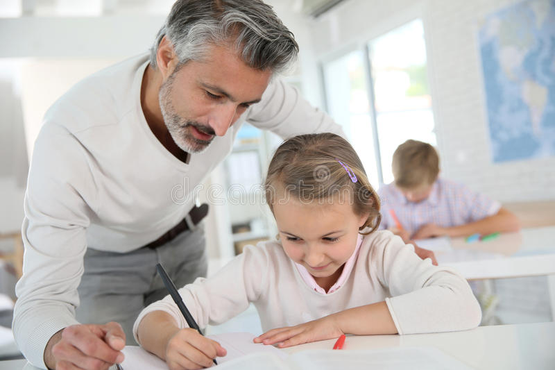 Ώριμος δάσκαλος που βοηθά τη νέα μαθήτρια στοκ εικόνες