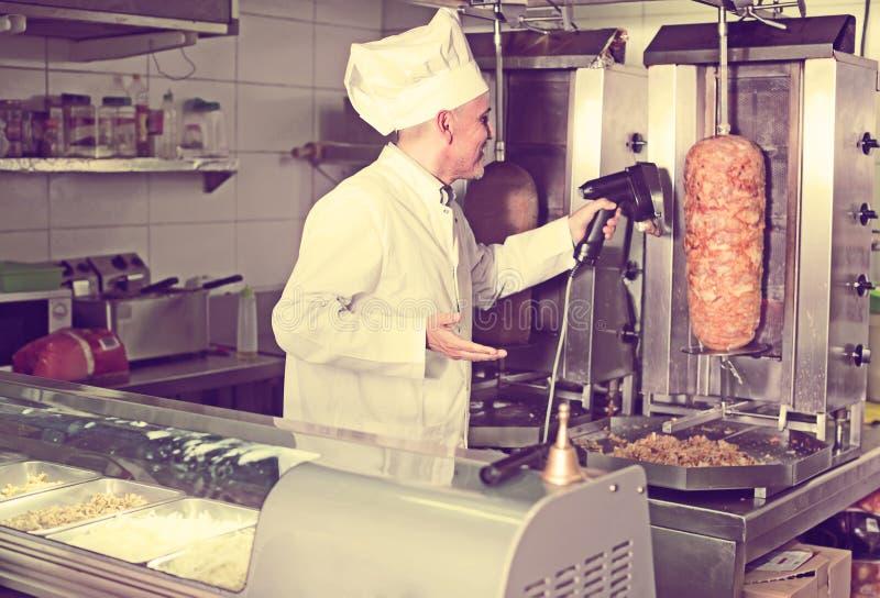 Ώριμος αρχιμάγειρας που τεμαχίζει kebab στο γρήγορο φαγητό στοκ φωτογραφίες