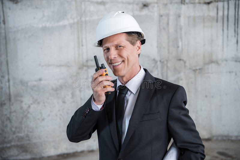 Ώριμος αρχιτέκτονας χρησιμοποιώντας walkie-talkie και χαμογελώντας στη κάμερα στοκ εικόνα