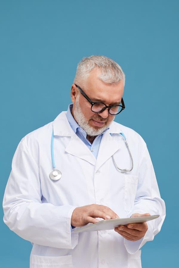 Ώριμος γιατρός με υπολογιστή tablet στοκ εικόνες
