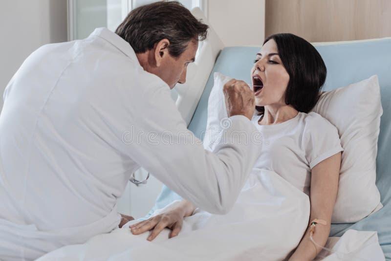Ώριμος γιατρός που ελέγχει το λαιμό του θηλυκού ασθενή στοκ εικόνες με δικαίωμα ελεύθερης χρήσης