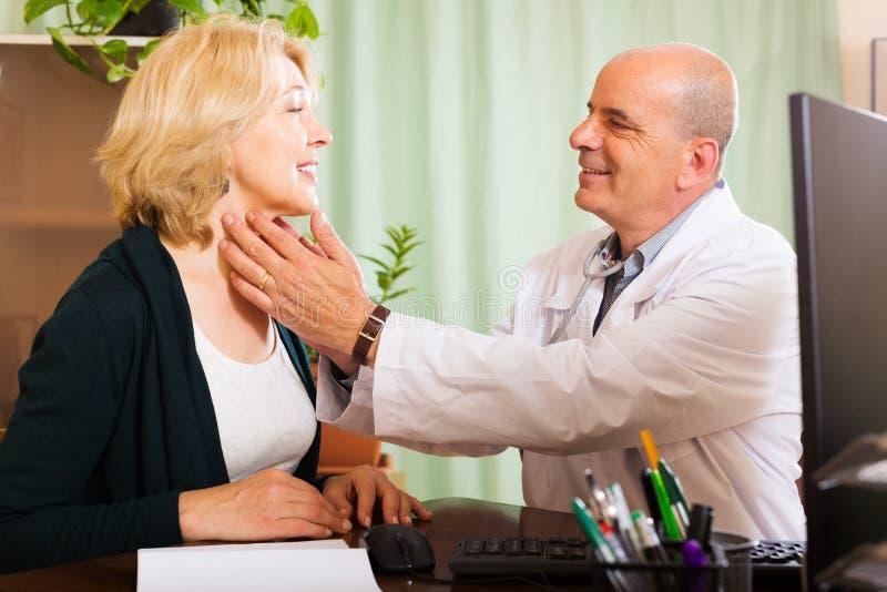 Ώριμος γιατρός που ελέγχει το θυροειδή της χαμογελώντας γυναίκας στοκ φωτογραφίες με δικαίωμα ελεύθερης χρήσης