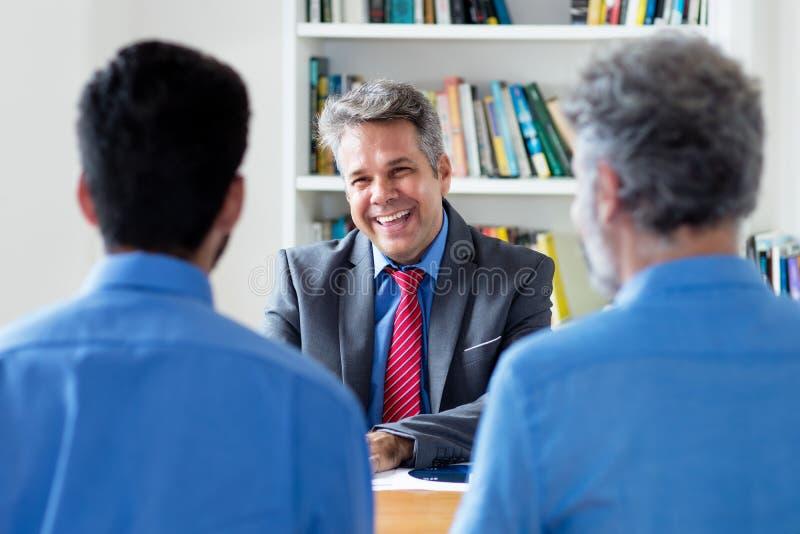 Ώριμος ενήλικος επιχειρηματίας που μιλά με τους συναδέλφους στοκ εικόνες