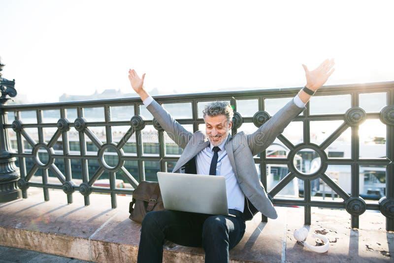 Ώριμος επιχειρηματίας με ένα lap-top σε μια πόλη στοκ φωτογραφίες