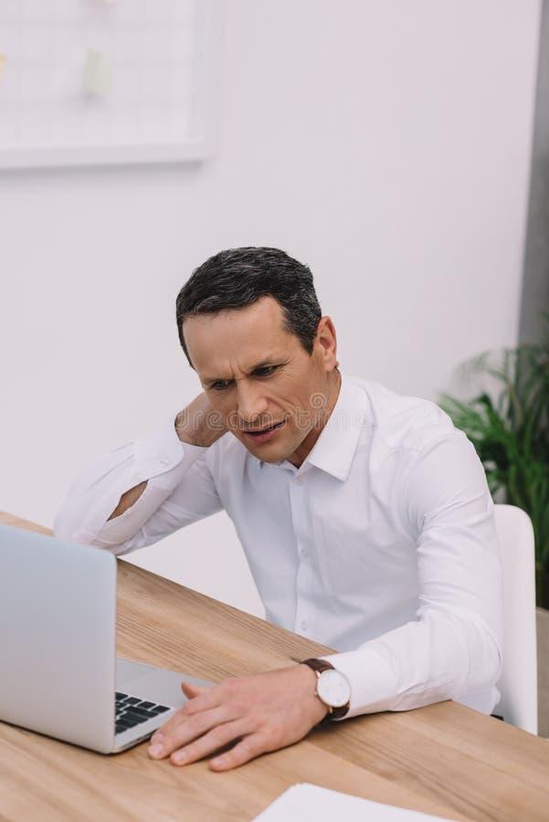 ώριμος επιχειρηματίας με τον πόνο λαιμών που εργάζεται με το lap-top στοκ εικόνες