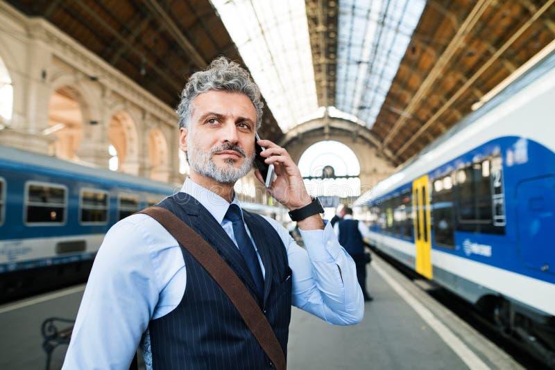 Ώριμος επιχειρηματίας με το smartphone σε έναν σταθμό τρένου στοκ φωτογραφίες