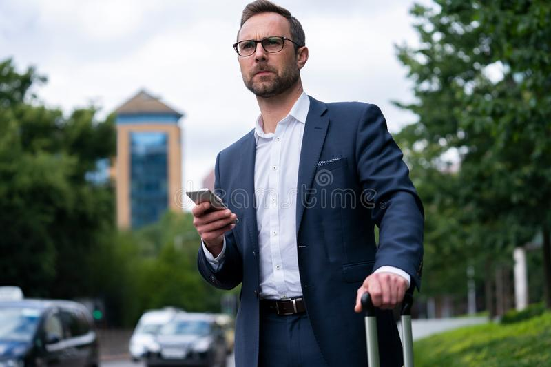 Ώριμος επιχειρηματίας που διατάζει το ταξί που χρησιμοποιεί το κινητό τηλέφωνο App στοκ εικόνα με δικαίωμα ελεύθερης χρήσης