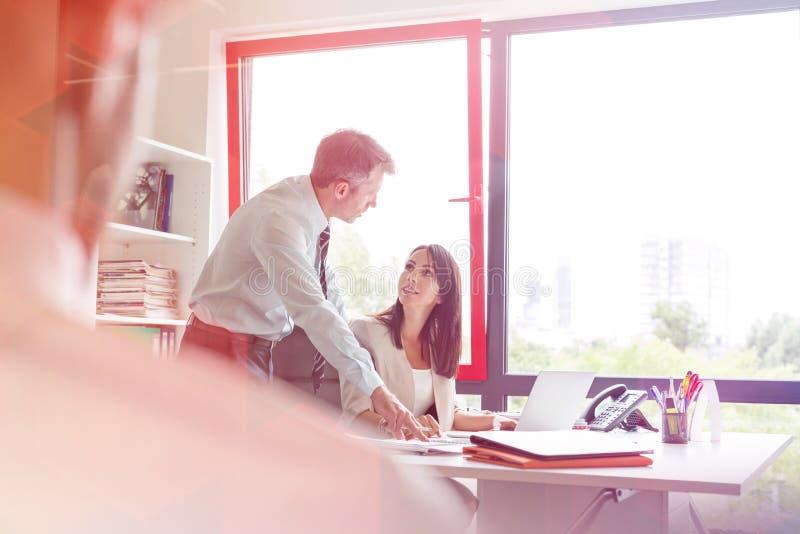Ώριμος επιχειρηματίας που εξηγεί στο συνάδελφο στο γραφείο στην αρχή στοκ εικόνες